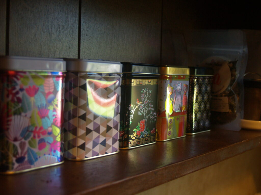 set of five small tea boxes and one or two bags of tea in the background