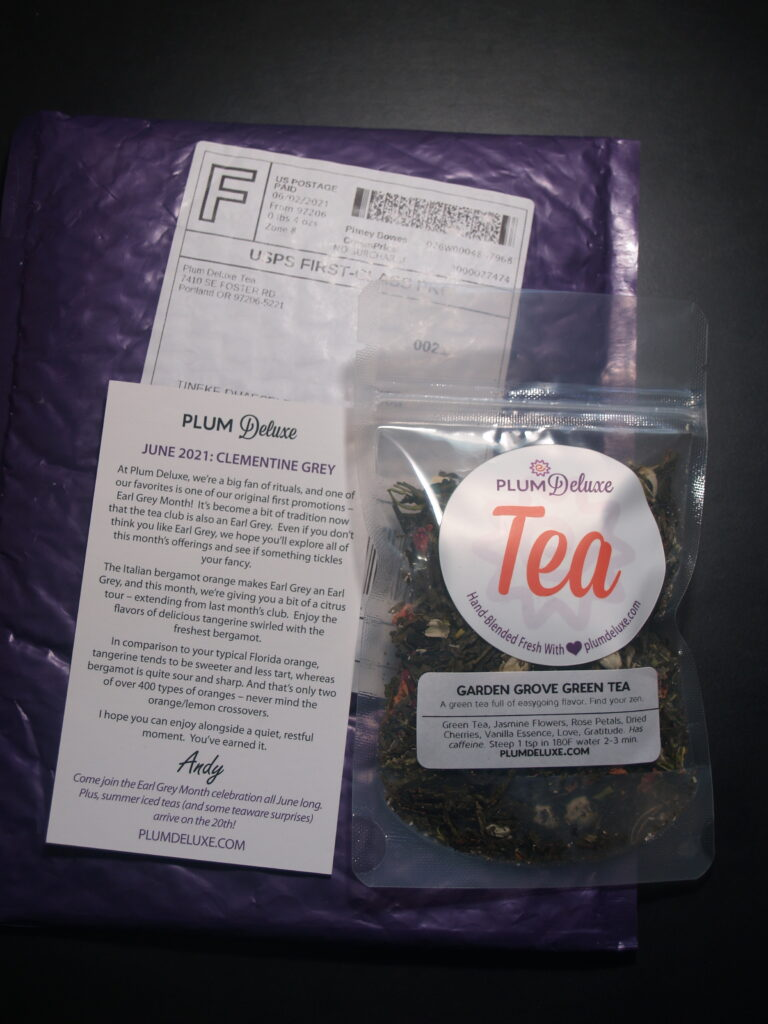 purple envelope with package from Plum Deluxe (Garden grove tea) on top, and a card explaining the tea