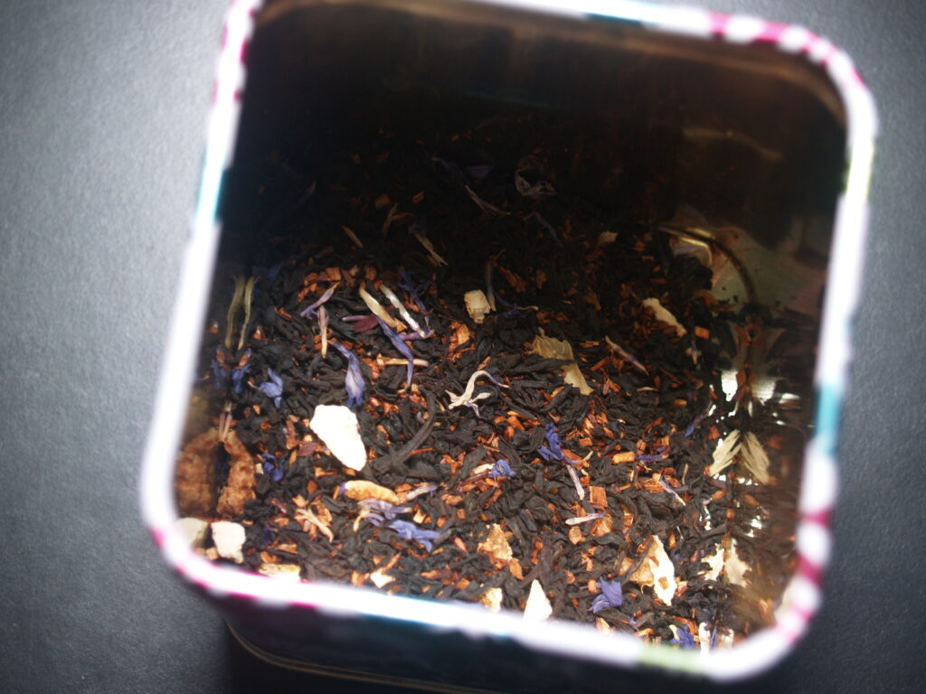 Close-up of black tea in a box, with specks of blue and white